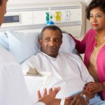 patient-in-hospital-bed-speaking-to-doctor-and-partner
