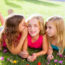 children friend girls group playing whispering on flowers grass